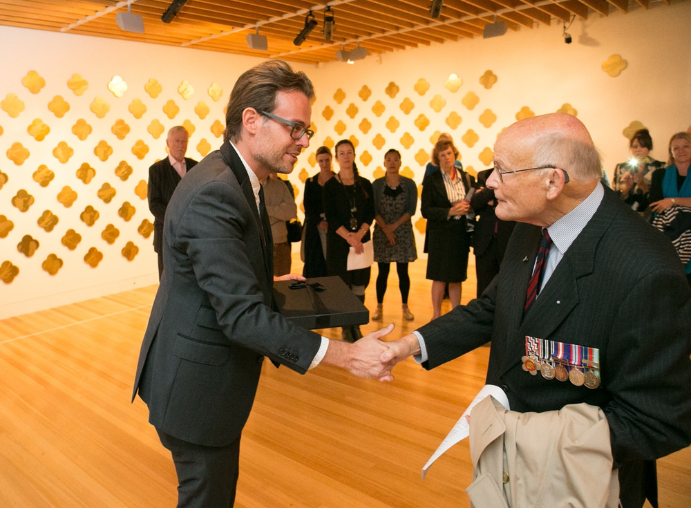 Keith Mitchell representing the New Zealand Sappers' Association (RNZE) receiving his Max Gimblett ONZM Remembrance artwork from Paul Baragwanath, Project Founder. Photography by Michael Hall copyright Te Papa Tongarewa.