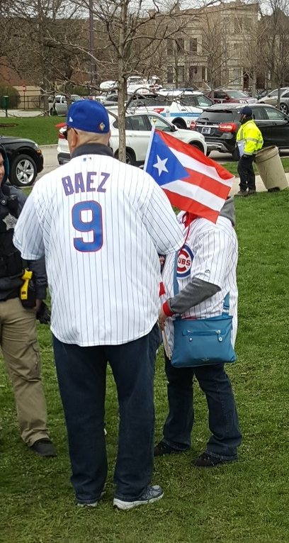 Fan wearing Javier Baez Cubs jersey number 9 and flying the flag of Puerto Rico