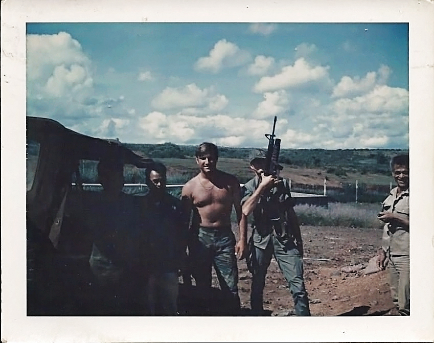 On the back of the photo it reads: 1305 hrs, Thu 23 July '70 V.C. Prisoner Of War Camp, East of Pleiku A.F.B. (my real dad is the one holding a gun) On far right, a POW interpreter, on my left, AIC Tarloton, a guard for POWs.  On his left, two V.C. who was captured up on Monkey Mountain which is not shown in this photo. Mirl Hobbs
