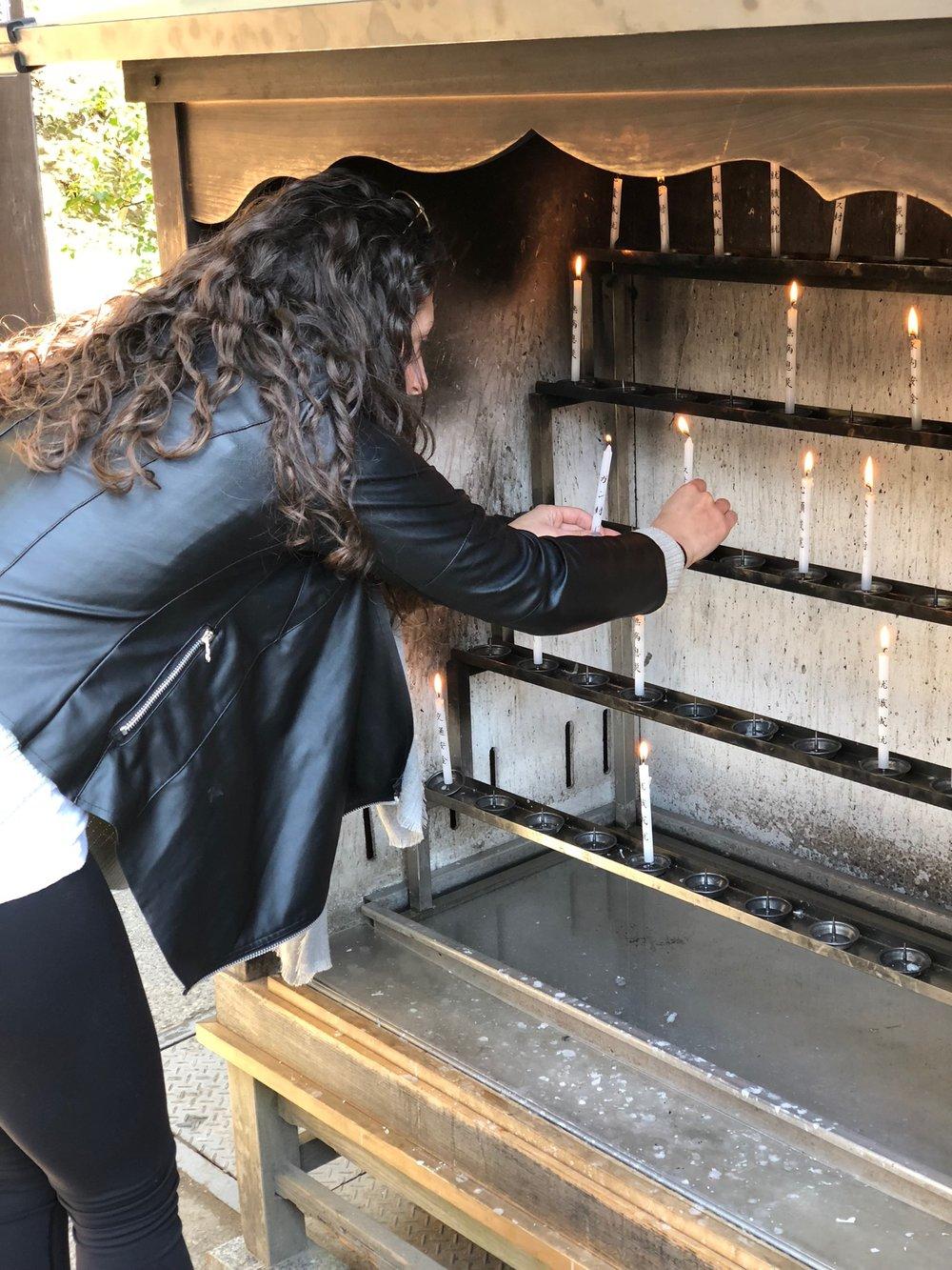 Alix lighting a prayer candle at the shrine on the grounds of Kinkaku-ji.