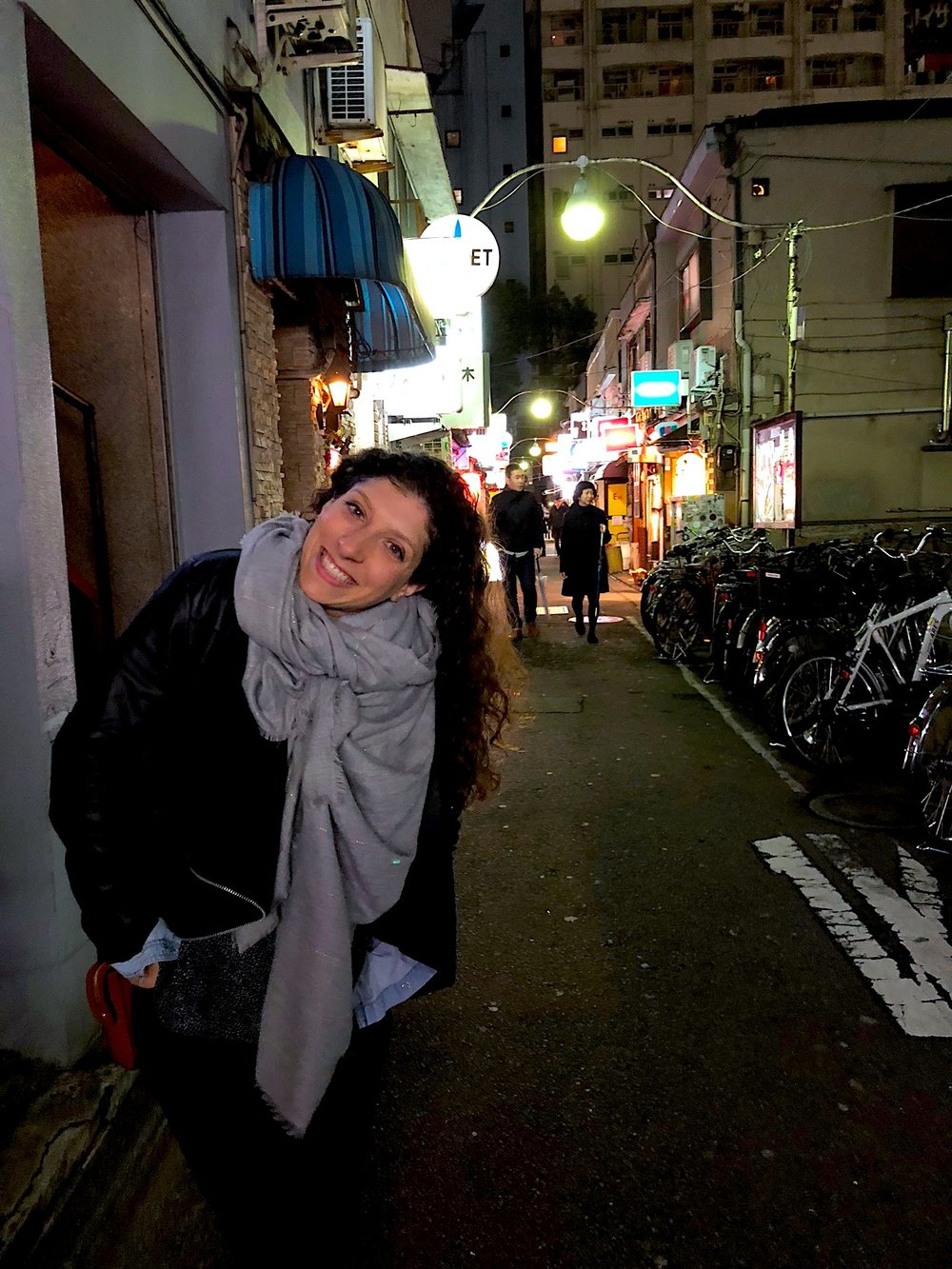"Alix poses at the end of one of the three small alleys that make up a very famous drinking area in Tokyo called ""Golden Gai"". 5 or so alleys near Shinjuku are home to hundreds of bars (literally), many with odd and specific themes to them (punk bars, western themed bars, etc.) We went to a few of them but they were ultimately expensive - many had a cover charge."