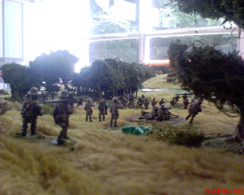 "A shot from behind the HQ, looking down toward the ford where the focus of the action was. The Boys ATR is doing proxy duty as a 2"" mortar. To the left you can see (just) 9th platoon entering cover while the remainder of 8th redeploys toward the centre right."