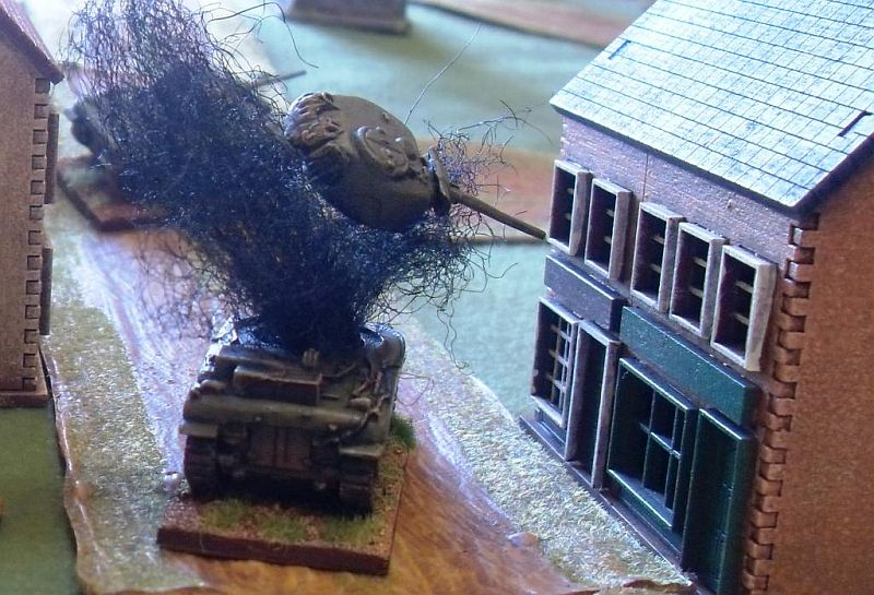 Action Shot: turret blown off the Sherman V by a PanzerFaust from the building next to it