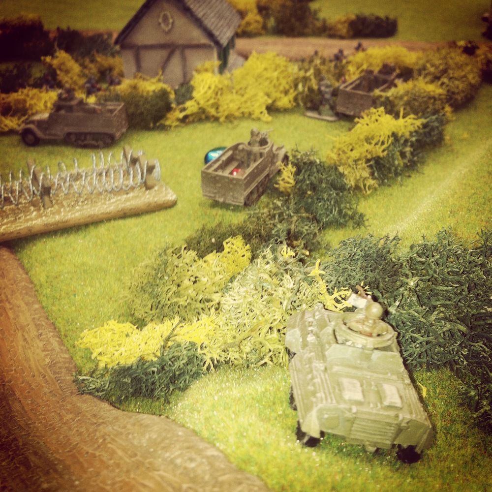 The recon unit moves to overlook the German position near the objective house as US half tracks roll into position