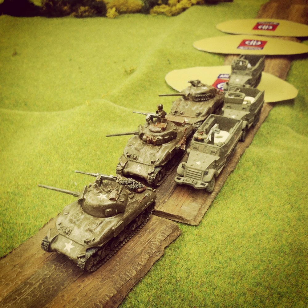 The column of US Shermans and infantry mounted in half tracks rush down the road