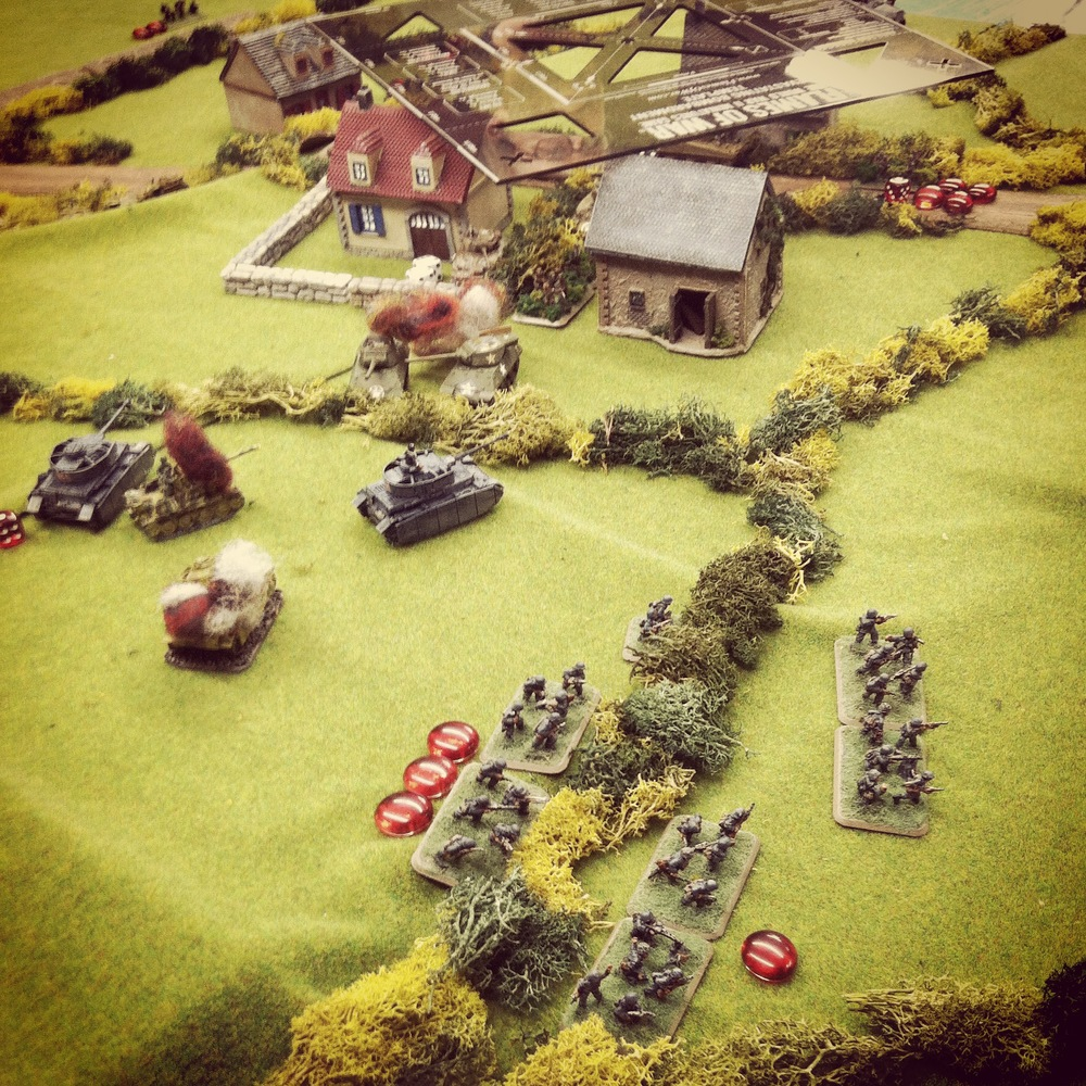 Panzer IVs destroy the final M10 Wolverine as German infantry rush to flank the town from the rear