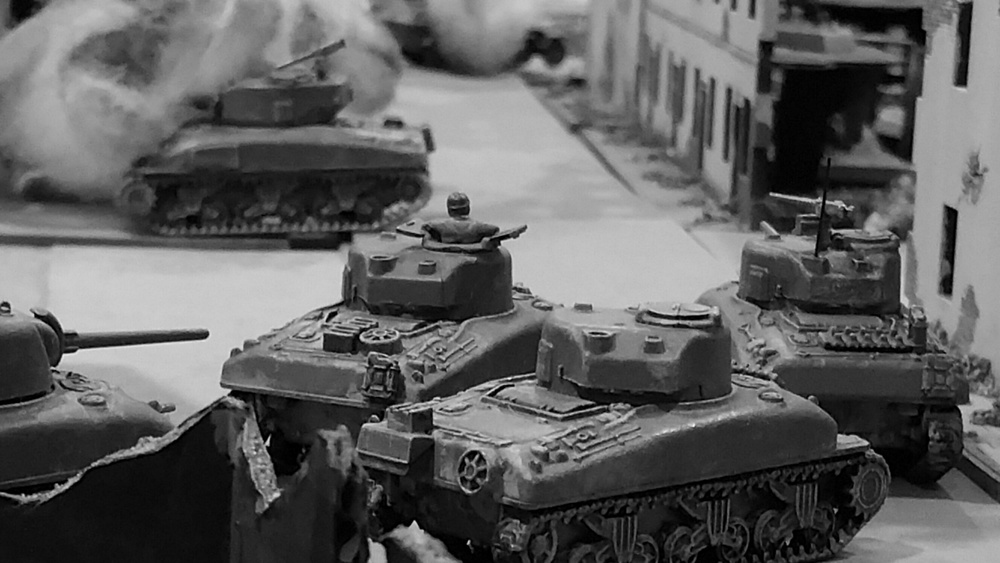 The surviving Shermans cower behind the last building in town, awaiting the last Tiger's approach.