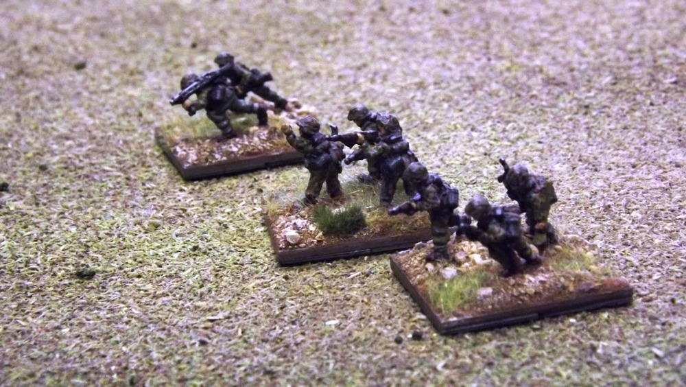 An SS Infantry Zug advances across open ground devoid of much cover