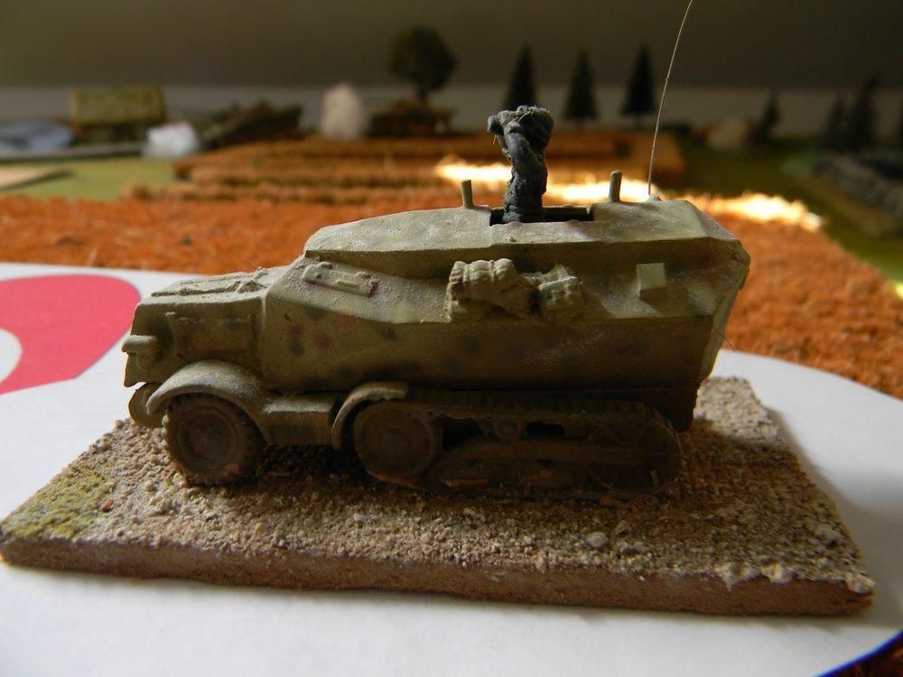 A German command half-track follows