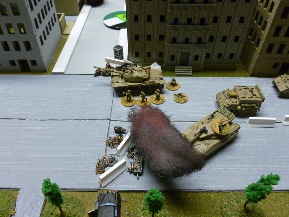 The Magach continues to fire on the T-34, guarded against RPGs by a squad of grunts.