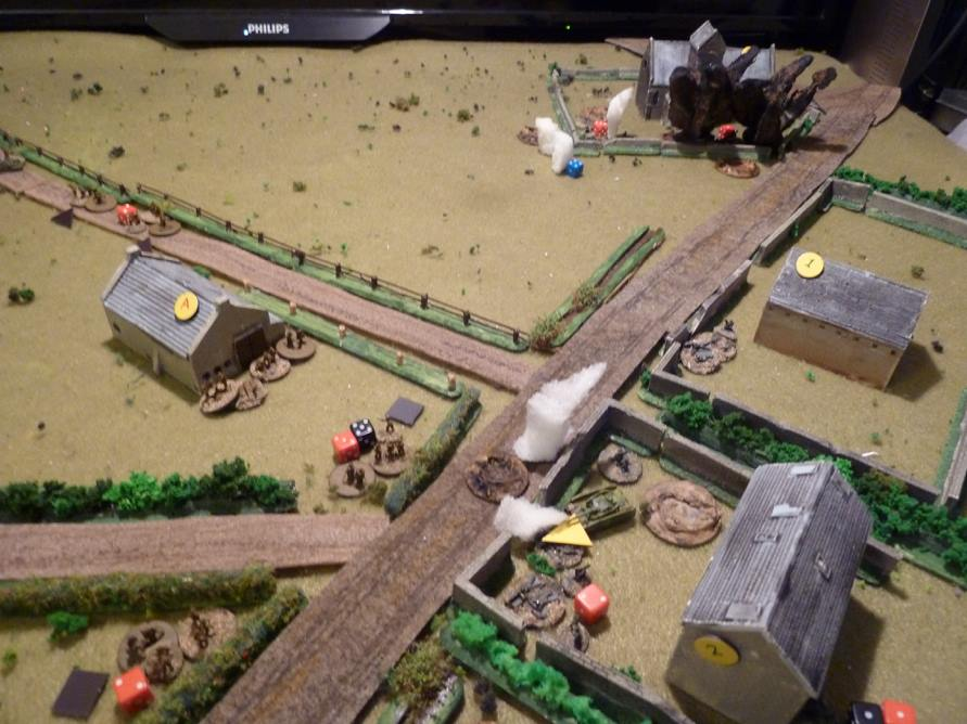 """The Germans in the churchyard get some 3"""" mortar attention, while the Vickers in a universal carrier just visible on the fenced track adds to their misery, firing at 'short' range, keeping them Pinned and slowly adding Shock despite the hard cover of the low wall around the church.   Massed return file from the British squads in the barn start to inflict Shock/kills in return on the platoon in the farm and MMG.   The Panzer IV suffers track damaged (the yellow triangle)."""