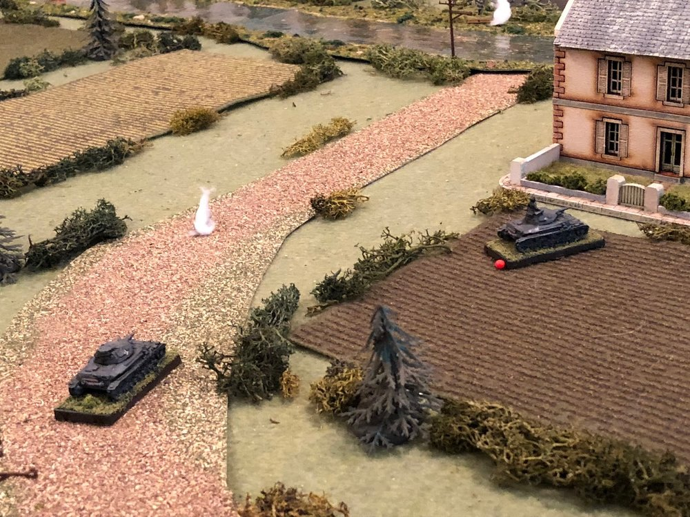 Which is enough to force Sgt Graebner's Pz IV off the road and into shelter behind Mlle Chevelle's house (red bead at right, from white puff at left, with Sgt Kapp's Pz IV at bottom left).