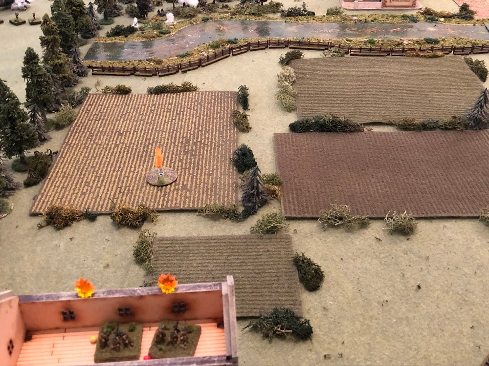 In the north, on the 2nd floor of the farmer's residence (bottom left), one MG team is still suppressed, but the other team, which is only pinned, gets back in the fight, spraying rounds into the northern treeline (top center left)...