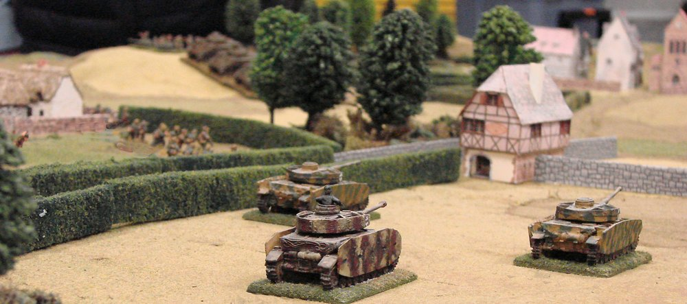 On the right, armor pounds the chateau with high explosives while the infantry drives into the adjacent woods.