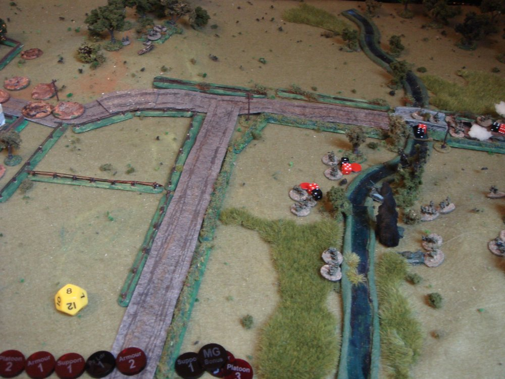 The supporting T-34s have silenced the MMG on the hill at the top, but...too late! The squads have routed back across the bridge.  Another MMG just out of shot to the left, again on a hill, now opens fire on the troops crossing the stream, and again the results are bloody! The red markers show suppressed troops.