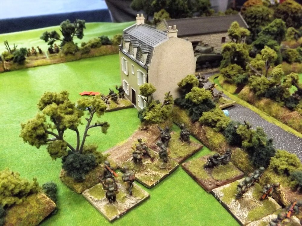 As the British tanks and heavy machine guns pour it on to the farm house other British infantry fire from across the road
