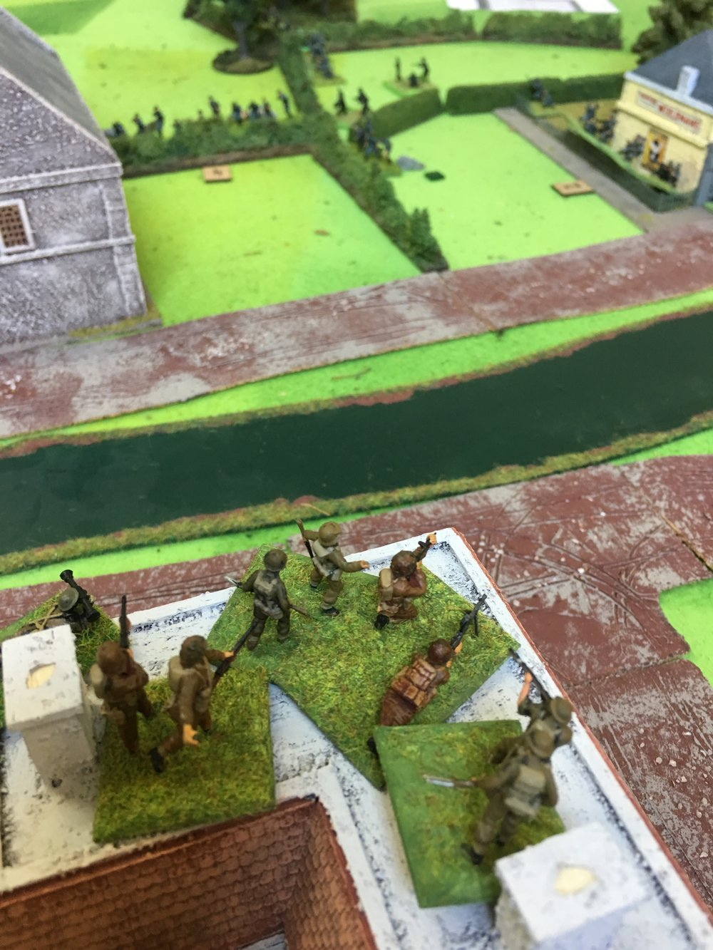 British defenders firing from the rooftops at the German attackers in the distance