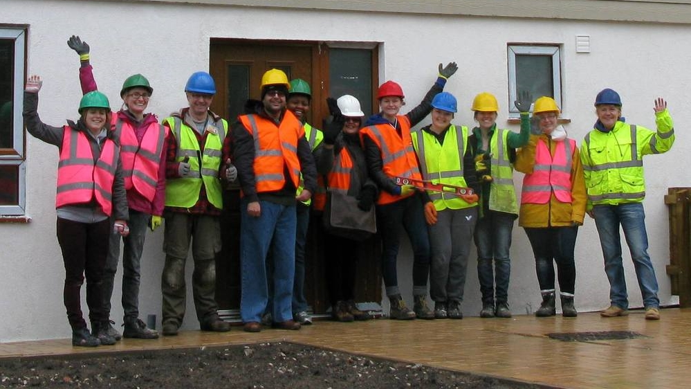 Some of HPBC's staff, home owners and volunteers celebrate the latest award shortlistings in front of the most recently completed Kingsley Road homes.