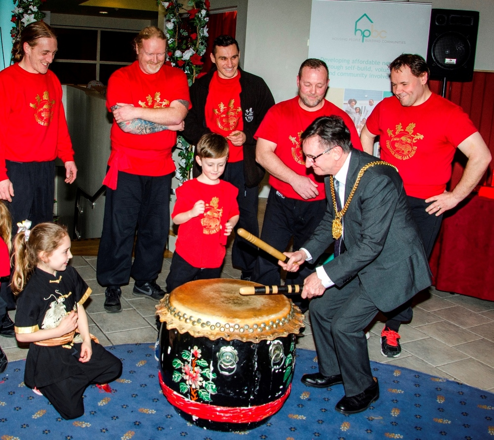 Liverpool's Lord Mayor Cllr Tony Concepcion bangs the drum, watched by members of Liverpool Hung Gar Kung Fu school.