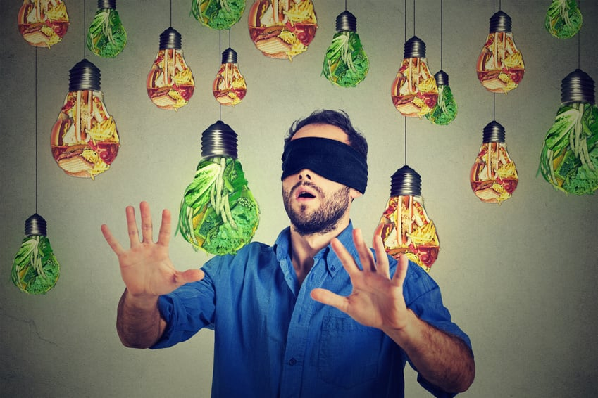 "Bild: ""Blindfolded man walking through light bulbs shaped as junk food and green vegetables"" 