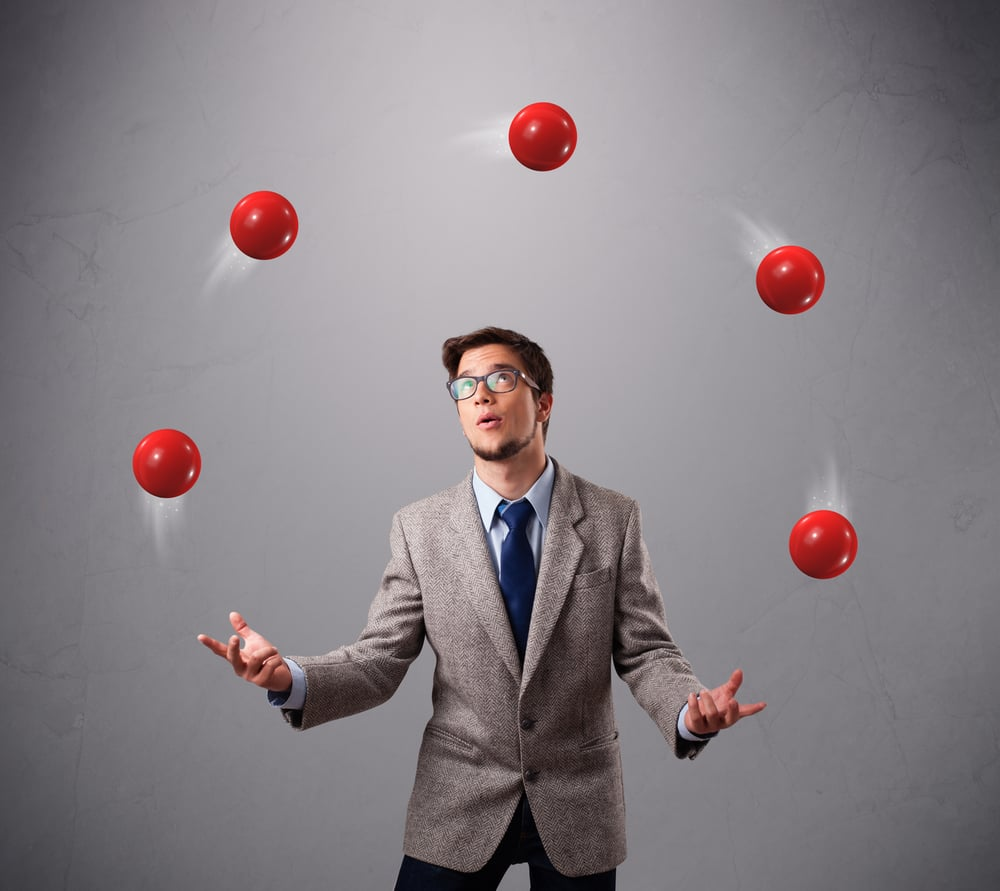 "Foto: ""young man standing and juggling with red balls"" 