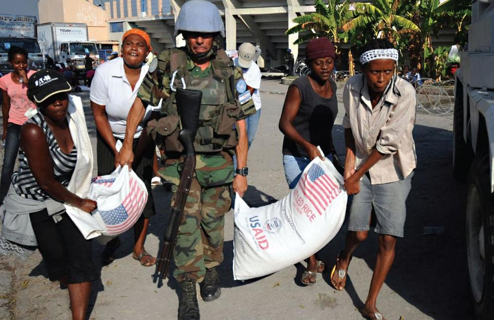 A United Nations peacekeeper helps locals move American food aid in the aftermath of the 2010 earthquake in Haiti.   Creative Commons / U.S. Navy