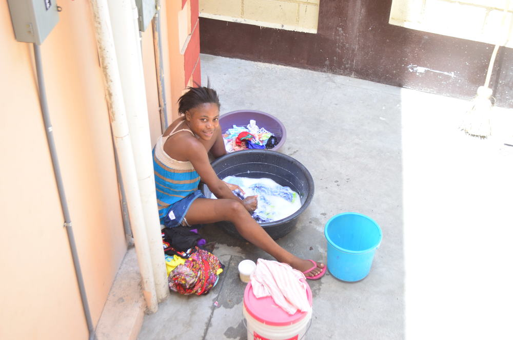 Claudie, 20, does laundry in the apartment courtyard. She lives here with her four siblings.