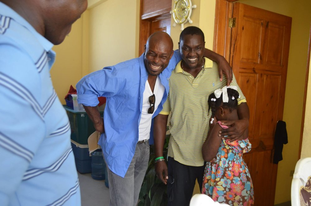 PADF Goodwill Ambassador Jimmy Jean-Louis gets to know Biene Johnson and his daughter in their new home.    (PADF, 2016)