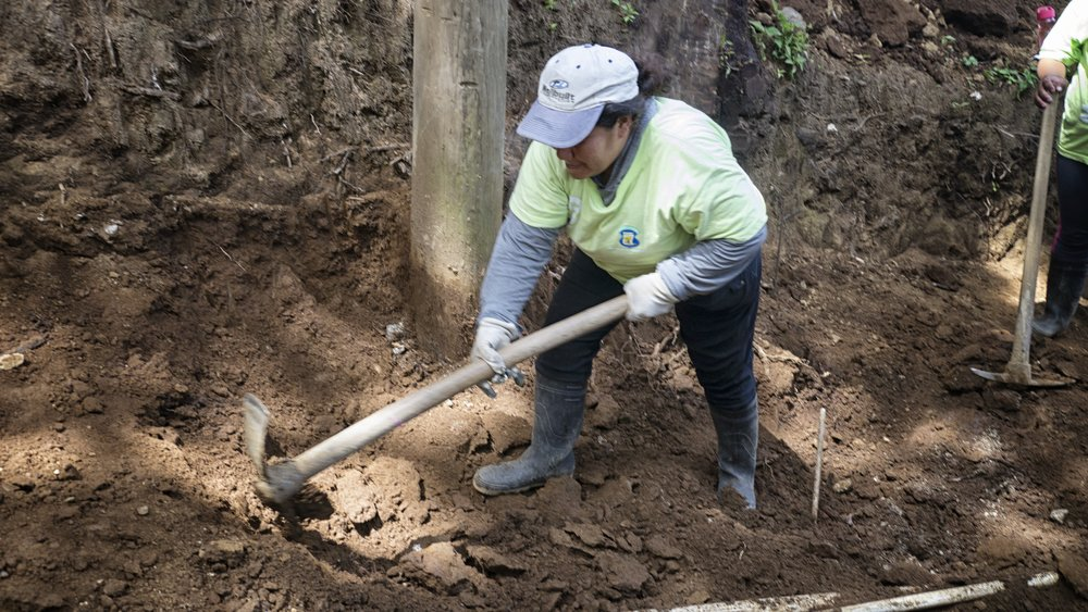 An El Campanero community member excavates the road construction area.