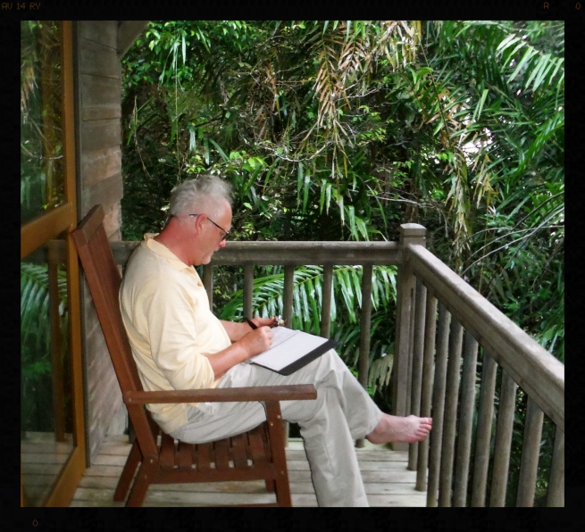 Photo by Scott Clemens. Christopher writing journal in a Treehouse in the canopy of a rainforest, Sarawak, Malaysia, Island of Borneo