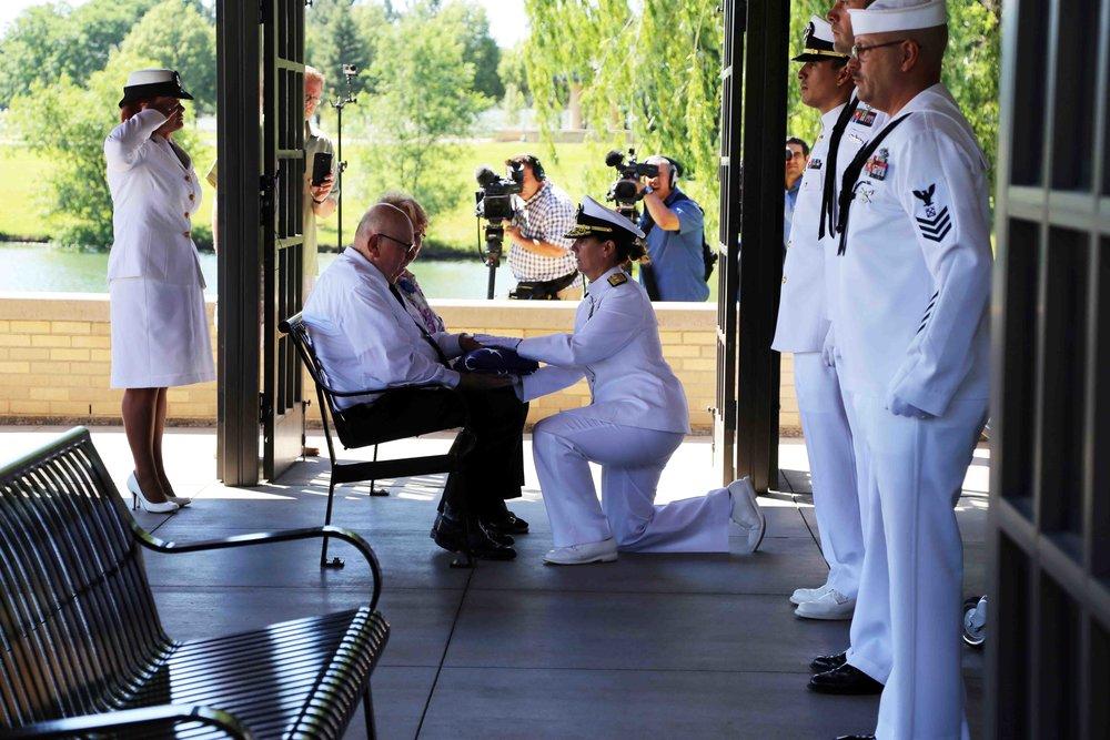 Rear Admiral Jackie McClellan presents a folded flag to Wallace Eakes' nephew, Gary Eakes. Photo courtesy of Erick Stowe.