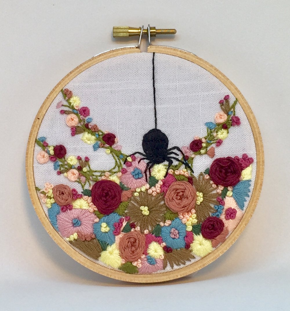 Spider in floral web embroidery hoop