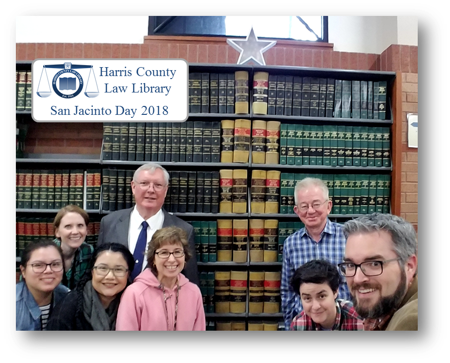 Staff at the Harris County Law Library take a #shelfie in front of a monographic replica of the San Jacinto Monument for San Jacinto Day 2018.