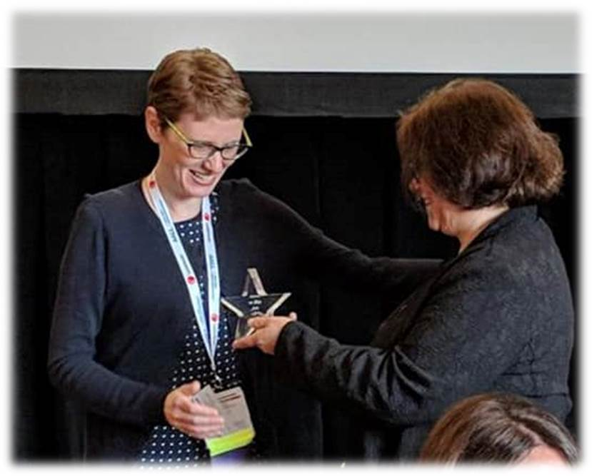 """Assistant law library Heather Holmes receives the American Association of Law Libraries Private Law Librarians and Information Professionals section """"Blog of the Year"""" award on behalf of Harris County Law Library from Saskia Mehlhorn, director of knowledge and libraries at Norton Rose Fulbright US."""