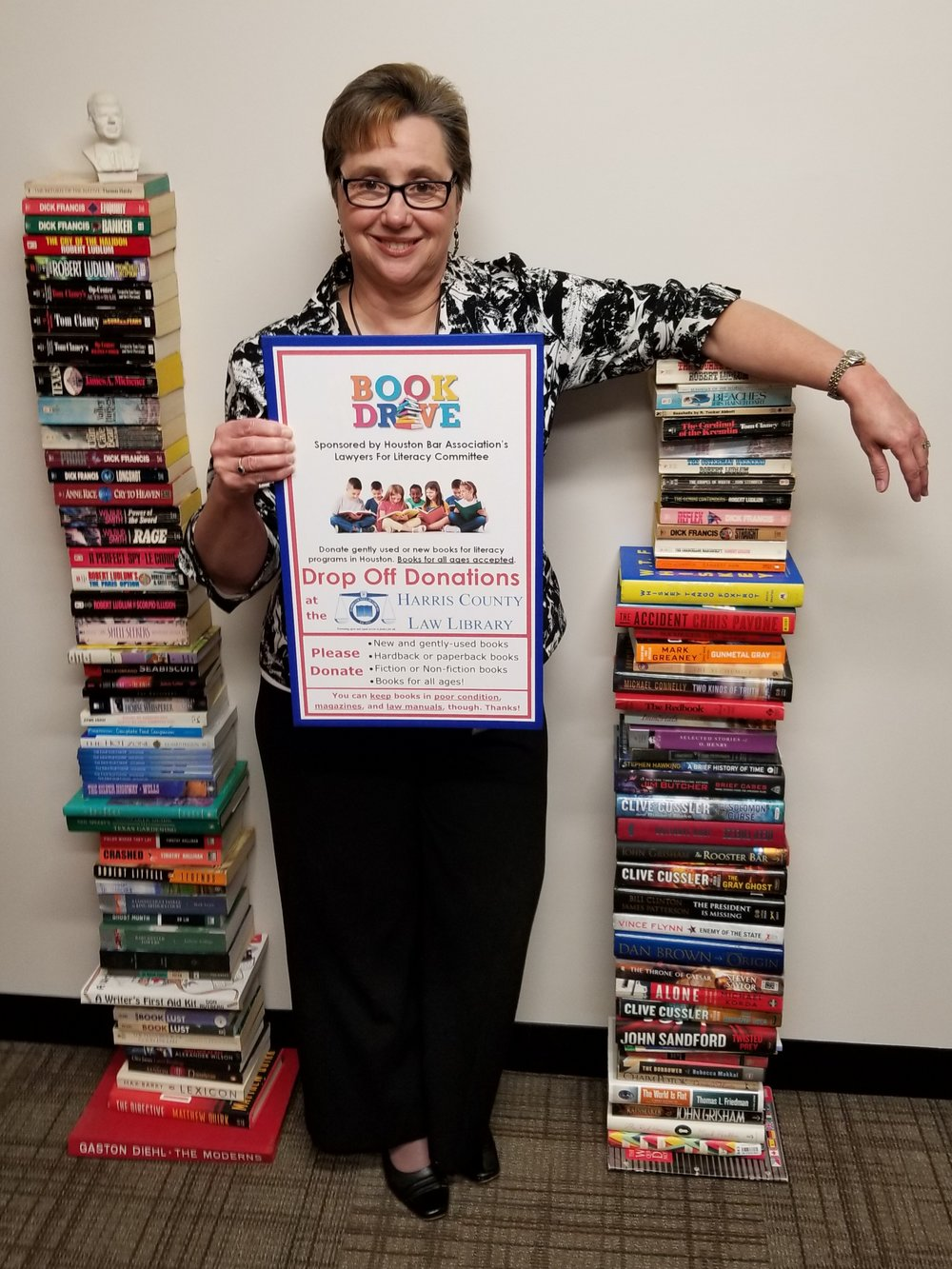 Harris County Law Library Director Mariann Sears with books donated for the HBA Lawyers for Literacy 25th Annual Book Drive
