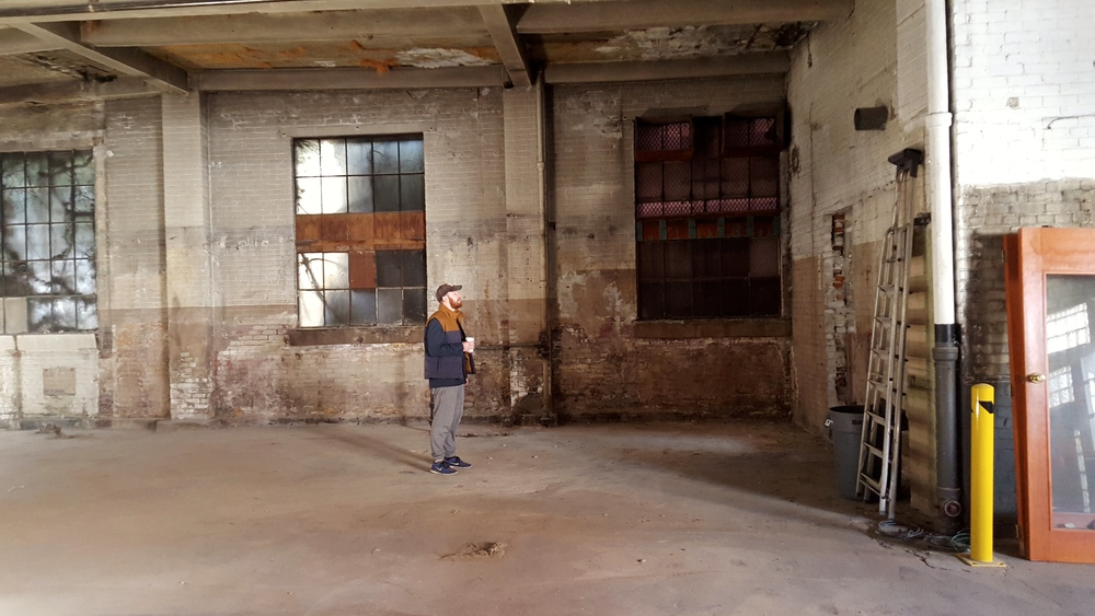 NOW : And here's AC - drinking his morning coffee and standing where the desk used to be. The taproom will occupy this space as well, and we're currently working on plans for the bar and tables