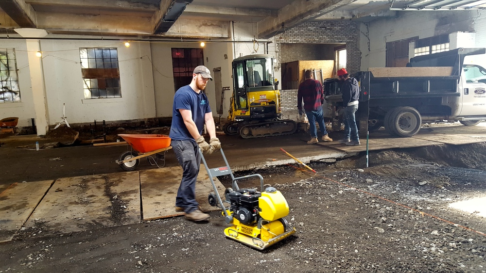 Most of the month was spent prepping the floors for sloping and drains - here AC compacts the dirt to get ready for the concrete pour
