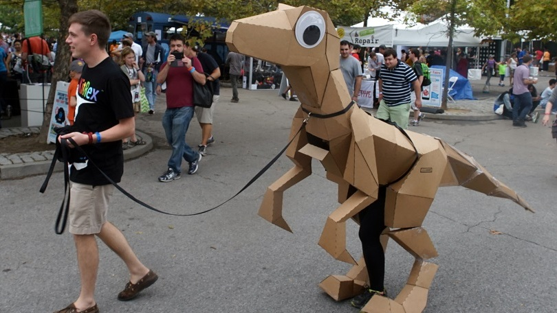 """A man takes a dinosaur for a stroll through Maker Faire. Is that a human leg I see?"""