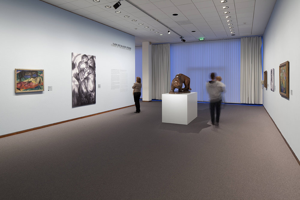"""Photograph of Tower of Blue Horses on display in Modern Times, 2010. Photo by Simon Vogel   Wall tag of black and white photograph:   Franz Marc   1880 München − 1916 Verdun   Tower of Blue Horses   1913   Oil on canvas   Acquired in 1919 from the artist's widow; exhibited until 1936 in the Kronprinzen-Palais; seized in 1937 and displayed at the """"Degenerate Art"""" exhibition in Munich; removed again from the exhibition after several days; confiscated before 1940 by Hermann Göring; lost since 1945"""