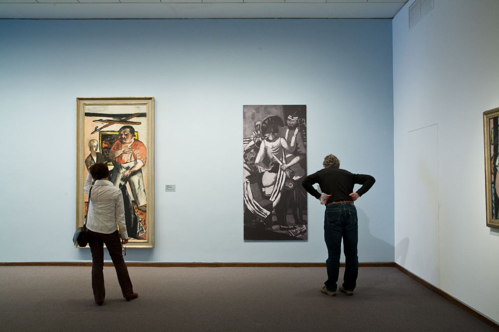"""Photograph of Parisian Carnival on display in Modern Times, 2010. Photo by Roman März   Wall Tag of black and white photograph:   Max Beckmann   1884 Leipzig − 1950 New York   Parisian Carnival   1930   Oil on canvas   Acquired from the artist in 1932; exhibited until 1933 in the Kronprinzen-Palais; seized in 1937 and exhibited in Munich at the """"Degenerate Art"""" exhibition; released in 1941 to the art dealer Karl Buchholz in Berlin; afterwards in the Günther Franke Collection, Munich; since 1974 in the Bayerische Staatsgemäldesammlungen in Munich, Pinakothek der Moderne, Stiftung Günther Franke   © VG Bild-Kunst, Bonn 2010"""
