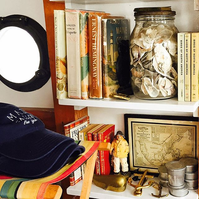 silver cups that flatten down, books on birds and a striped fabric stool, all on board the @grandbanksnyc for #mategallery #nyc #oysterbar #grandbanks
