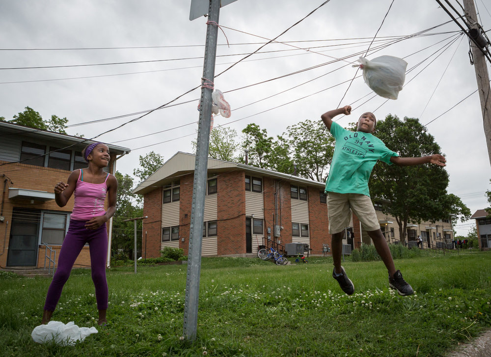 Zi'Teriyon Gray, 11, jumps for a hit while playing tetherball against his cousin, Alahzeyai Harvey, 11, on their block Sunday, May 10, 2015.