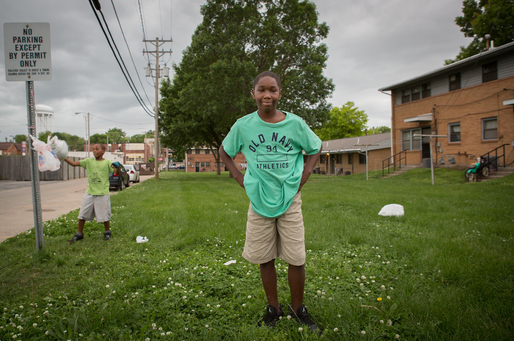 Zi'Teriyon Gray, 11, poses for an impromptu portrait while his brother, Zi'Ion Gray, 9, plays behind.