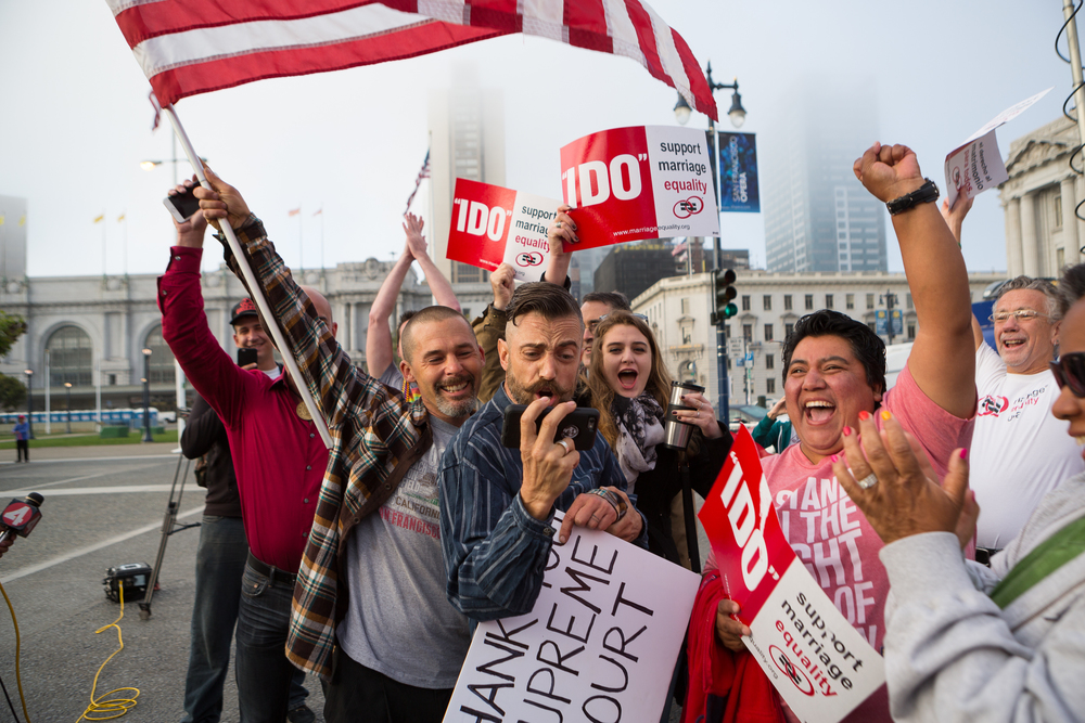 Joe Capley-Alfano (holding phone), husband Frank Capley-Alfano (holding flag), Laura Carnosa (in pink) and others cheer moments after finding out the Supreme Court's positive ruling on same-sex marriage in front of City Hall in San Francisco, California, on Friday, June 26, 2015.