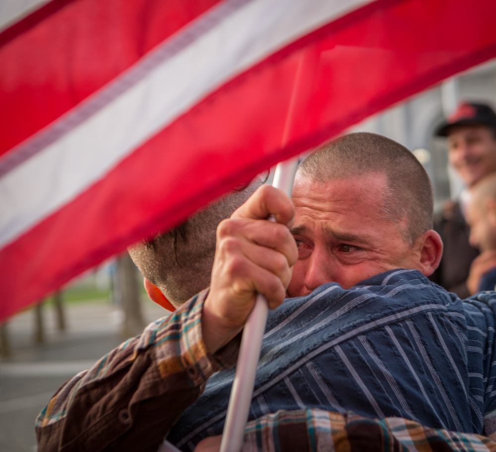 Frank Capley-Alfano raises an American flag while embracing husband Joe Capley-Alfano moments after finding out the Supreme Court's positive ruling on same-sex marriage in front of City Hall in San Francisco, California, on Friday, June 26, 2015.