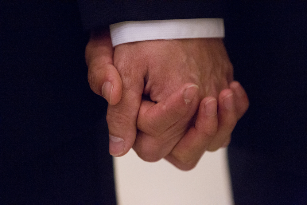 Mark Streeter and partner Hai Nguyen hold hands while waiting to receive a marriage license at City Hall in San Francisco, California, shortly after the Supreme Court's ruling in favor of same-sex marriage on Friday, June 26, 2015.
