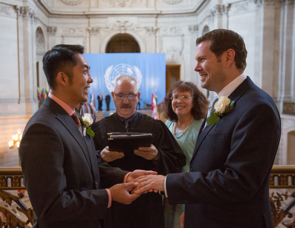 Hai Nguyen (left) and Mark Streeter are married by Deputy Marriage Commissioner John Pleskach at City Hall in San Francisco, California, shortly after the Supreme Court's ruling in favor of same-sex marriage on Friday, June 26, 2015. The Fourteenth Amendment requires a state to license a marriage between two people of the same sex. Mark's mother, Linda Streeter, is seen in the background.