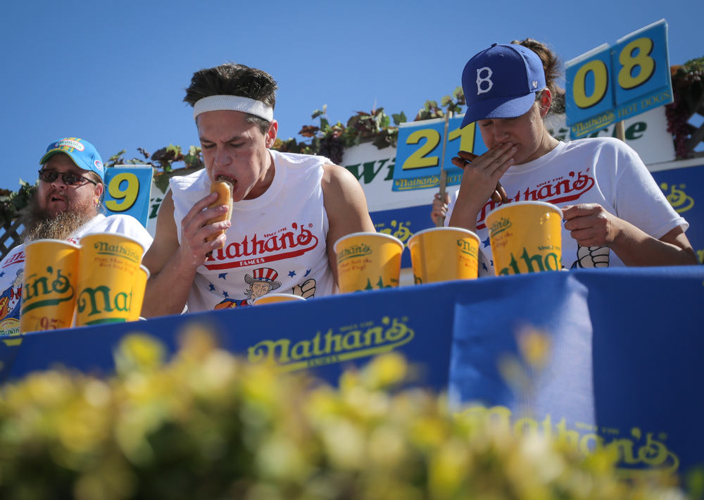 """Brian Dudzinksi (center) pushes through the pain during Nathan's Famous Hot Dog Eating Qualifier at Sonoma Raceway on Sunday, June 28, 2015. Dudzinksi won with 21.5 dogs eaten, besting a field of competition that included Lesley Ryder (right) and Jon Davis (left). The qualifier was a """"Major League Eating"""" event."""
