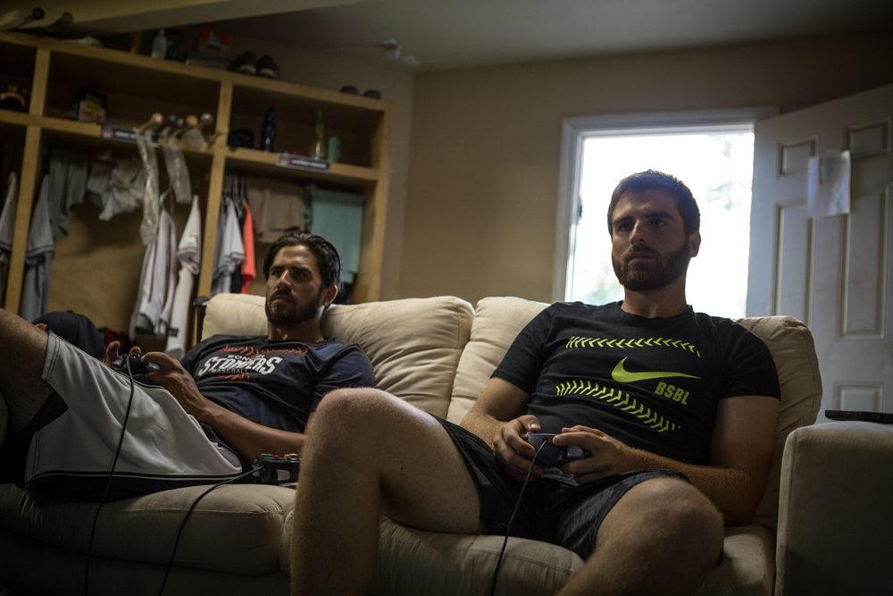 Sonoma Stompers starting pitcher Sean Conroy (right) plays video games with teammate Erik Gonsalves before a game against the Pittsburg Diamonds at Arnold Field in Sonoma, California, on Tuesday, July 7, 2015. Conroy is baseball's first active professional player to come out as gay.