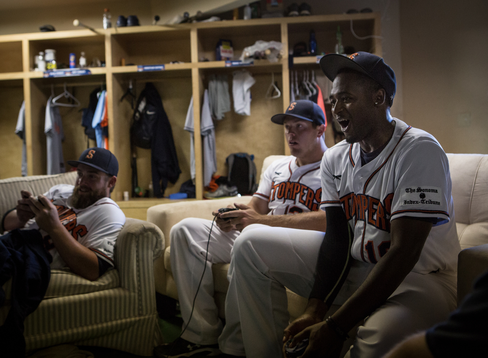 From right: Sonoma Stompers players Mike Jackson Jr., Andrew Parker and Isaac Wenrich play video games in the clubhouse before a game against the Pittsburg Diamonds at Arnold Field in Sonoma, CA, on Tuesday, July 7, 2015. The Stompers blew a 9th inning lead.